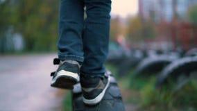 Tennisschoenen die van de speelplaats de dichte omhooggaande jongen op de langzame motie van autobanden lopen stock video