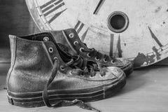 Tennisschoenen en een klok met zwart-wit stock fotografie
