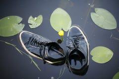 Tennisschoenen in het water stock afbeeldingen