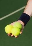 Tennisspelare som rymmer tre bollar Arkivbilder