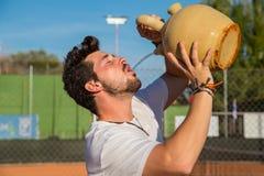 Tennisspelaredricksvatten från krukan på domstolen Arkivfoto