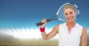 Tennisspeler die tegen stadion met verstralers en blauwe hemel glimlachen Royalty-vrije Stock Afbeelding