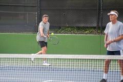 Tennisspieler, der vom Zweigericht schlägt Lizenzfreie Stockfotos