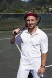 Tennisspieler lächelt mit seinem Schläger Stockbilder