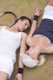 Tennissportbegrepp: Unga par av tennisspelare som vilar på Arkivfoto