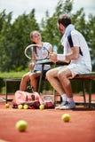 Tennistrainer die met vrouwelijke speler spreken stock fotografie