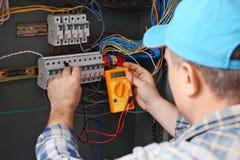 Tensão de medição do eletricista maduro na placa de distribuição foto de stock