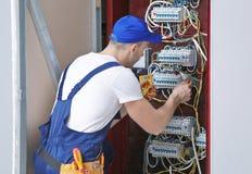 Tensão de medição do eletricista na placa foto de stock