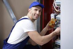 Tensão de medição do eletricista na placa fotos de stock royalty free