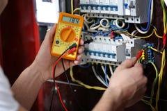 Tensão de medição do eletricista na placa de distribuição fotos de stock