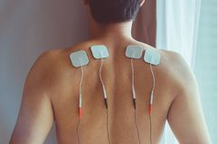 TENS treatment in physical therapy. Young man with TENS on his b stock images