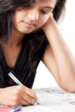 Tense beautiful indian girl writing on print paper Royalty Free Stock Photos
