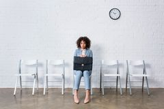 Tense businesswoman with briefcase sitting on chair. And waiting stock photo