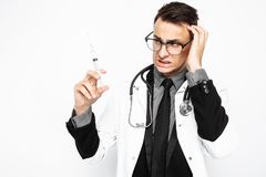 Tense doctor in glasses, with a stethoscope around his neck, holding a syringe for injection, looking at him with fear, isolated stock photo
