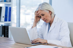 Tense female doctor working on her laptop Stock Photos