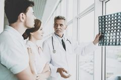 Tense Male Doctor Indicates on Image of Roentgen. royalty free stock images