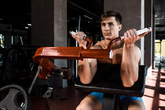 Tense muscles of hands under load. Man doing exercise for biceps in the gym. Stock Photography