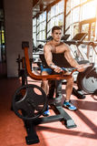 Tense muscles of hands under load. Man doing exercise for biceps in the gym. Royalty Free Stock Photos
