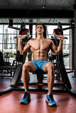Tense muscles of hands under load. Man doing exercise for biceps in the gym. Royalty Free Stock Images