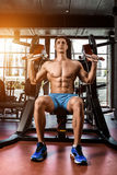 Tense muscles of hands under load. Man doing exercise for biceps in the gym. Work on tell muscles on the simulator. Photos for sporting magazines, posters and Stock Photos