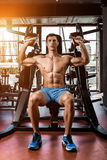 Tense muscles of hands under load. Man doing exercise for biceps in the gym. Work on tell muscles on the simulator. Photos for sporting magazines, posters and Stock Photography