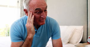 Tense senior man sitting on bed in bedroom stock footage