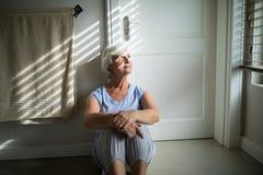 Tense senior woman looking through window in bedroom Royalty Free Stock Image