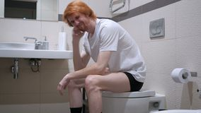 Tense Upset Redhead Man Sitting in Toilet, Commode. 4k , high quality stock video footage