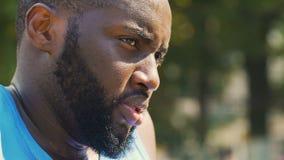 Tense y descontentó al hombre afroamericano que mira alrededor, discriminación almacen de metraje de vídeo