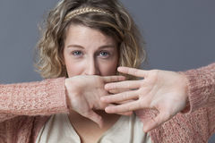 Tense young blonde woman protecting herself Royalty Free Stock Image
