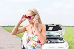 Tensed женщина используя сотовый телефон на проселочной дороге с сломанный вниз с автомобиля в предпосылке Стоковое Изображение RF