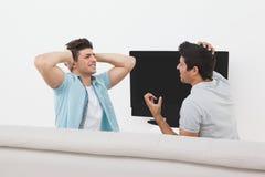 Tensed поклонники футбола смотря ТВ Стоковые Изображения RF