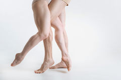 Tensed ballet dancers legs performing in the white colored room royalty free stock images