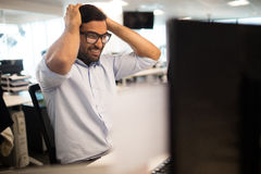 Tensed businessman clenching teeth in office Stock Photo