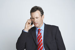 Tensed Businessman Communicating On Cell Phone Royalty Free Stock Photos