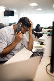 Tensed businessman talking on land line at desk. Tensed businessman with head in hand talking on land line at desk in office Stock Photo