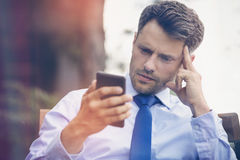 Tensed businessman using mobile phone Royalty Free Stock Photography