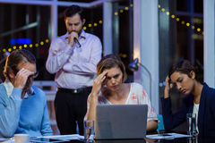 Tensed businesspeople working on laptop Royalty Free Stock Photo