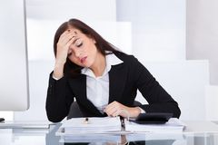 Tensed businesswoman calculating tax Royalty Free Stock Photo