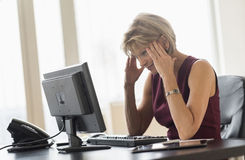 Tensed Businesswoman Looking At Computer At Desk Stock Photo