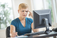 Tensed Businesswoman Working On Desktop PC Royalty Free Stock Photos