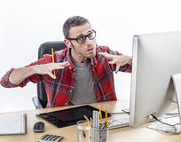 Tensed casual entrepreneur with eyeglasses expressing his frustration and exasperation. With nervous hands at his graphic designer desk, white background Royalty Free Stock Photos