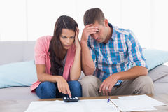 Tensed couple calculating home finances. At table in house Stock Photography