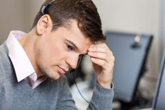 Tensed Customer Service Representative In Call. Closeup of tensed male customer service representative in call center Royalty Free Stock Images