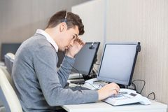 Tensed Customer Service Representative At Desk. Side view of tensed customer service representative using landline phone at desk in office royalty free stock photos