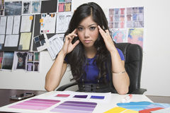 Tensed Female Fashion Designer At Desk Royalty Free Stock Photo
