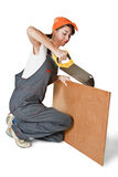Tensed girl sawing board Royalty Free Stock Photography