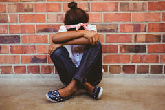 Tensed girl sitting against brick wall in school corridor Royalty Free Stock Image
