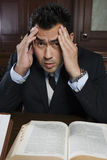 Tensed Male Advocate With Law Book. Portrait of a tensed male advocate sitting with law book in the courtroom Stock Photo