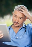 Tensed Male Caretaker Using Tablet PC. In nursing home porch stock images